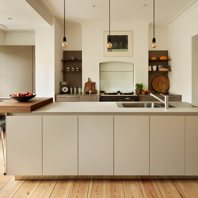 Kitchen - contemporary light wood floor kitchen idea in Oxfordshire with a double-bowl sink, flat-panel cabinets, white cabinets and an island