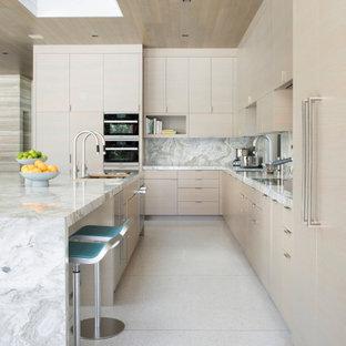 サンフランシスコの大きいコンテンポラリースタイルのおしゃれなキッチン (アンダーカウンターシンク、フラットパネル扉のキャビネット、淡色木目調キャビネット、御影石カウンター、白いキッチンパネル、石スラブのキッチンパネル、シルバーの調理設備の、テラゾの床、白い床、白いキッチンカウンター) の写真