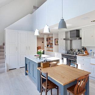 Modelo de cocina comedor lineal, nórdica, con fregadero sobremueble, armarios estilo shaker, puertas de armario blancas, electrodomésticos de acero inoxidable, suelo de madera clara y una isla
