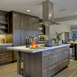 Пример оригинального дизайна интерьера: огромная п-образная кухня в современном стиле с плоскими фасадами, столешницей из кварцевого композита, фартуком из стеклянной плитки, полом из керамогранита, островом, техникой под мебельный фасад и коричневыми фасадами