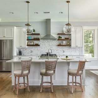 Large beach style eat-in kitchen remodeling - Large coastal u-shaped light wood floor eat-in kitchen photo in Charleston with an undermount sink, shaker cabinets, white cabinets, gray backsplash, stainless steel appliances, an island, gray countertops and quartzite countertops