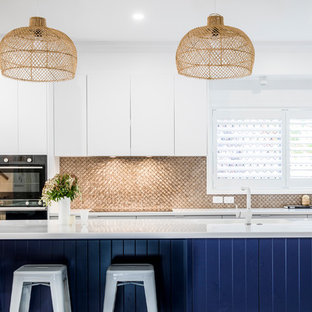 Photo of a mid-sized contemporary galley open plan kitchen in Townsville with an undermount sink, flat-panel cabinets, blue cabinets, quartz benchtops, metallic splashback, mosaic tile splashback, stainless steel appliances, with island and white benchtop.