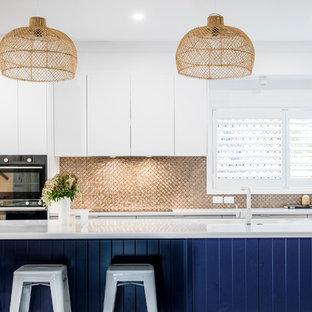 Inspiration för ett mellanstort funkis vit vitt kök, med en undermonterad diskho, släta luckor, blå skåp, bänkskiva i kvarts, stänkskydd med metallisk yta, stänkskydd i mosaik, rostfria vitvaror och en köksö