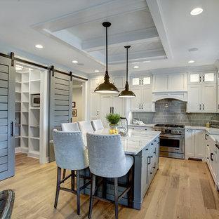 Klassische Küche in L-Form mit Landhausspüle, Schrankfronten im Shaker-Stil, weißen Schränken, Marmor-Arbeitsplatte, Küchenrückwand in Grau, Rückwand aus Metrofliesen, Küchengeräten aus Edelstahl, hellem Holzboden, Kücheninsel und beigem Boden in Grand Rapids