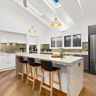 Inspiration for an expansive contemporary open plan kitchen in Other with a double-bowl sink, concrete benchtops, metallic splashback, porcelain splashback, stainless steel appliances, medium hardwood floors, with island, brown floor and exposed beam.