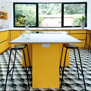 Идея дизайна: угловая кухня среднего размера в современном стиле с обеденным столом, плоскими фасадами, желтыми фасадами, столешницей из ламината, островом, белой столешницей, двойной раковиной, техникой из нержавеющей стали и разноцветным полом