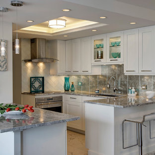Inspiration for a small transitional u-shaped kitchen in Chicago with an undermount sink, shaker cabinets, white cabinets, quartzite benchtops, metallic splashback, glass tile splashback, stainless steel appliances, porcelain floors and a peninsula.