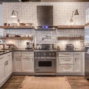 アトランタのインダストリアルスタイルのおしゃれなペニンシュラキッチン (アンダーカウンターシンク、シェーカースタイル扉のキャビネット、白いキャビネット、白いキッチンパネル、シルバーの調理設備、無垢フローリング) の写真