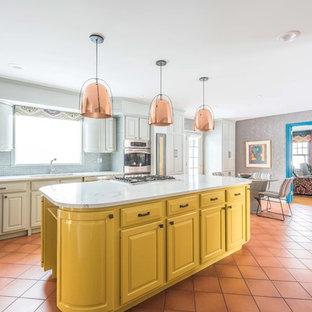 ミネアポリスの広いコンテンポラリースタイルのおしゃれなキッチン (レイズドパネル扉のキャビネット、グレーのキャビネット、クオーツストーンカウンター、グレーのキッチンパネル、ガラスタイルのキッチンパネル、シルバーの調理設備、テラコッタタイルの床、赤い床、白いキッチンカウンター、アンダーカウンターシンク) の写真