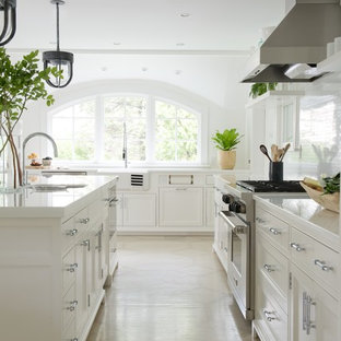 Kitchen - country galley kitchen idea in New York with a farmhouse sink, recessed-panel cabinets, white cabinets, white backsplash, stainless steel appliances and an island