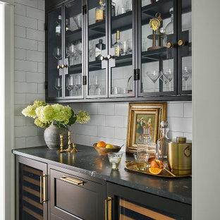 Стильный дизайн: кухня среднего размера в стиле неоклассика (современная классика) с раковиной в стиле кантри, фасадами в стиле шейкер, столешницей из кварцита, белым фартуком, фартуком из плитки кабанчик, техникой под мебельный фасад, паркетным полом среднего тона, островом, черной столешницей, кладовкой и черными фасадами - последний тренд