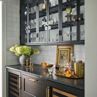 Mid-sized transitional kitchen pantry inspiration - Mid-sized transitional galley medium tone wood floor kitchen pantry photo in Chicago with a farmhouse sink, shaker cabinets, quartzite countertops, white backsplash, subway tile backsplash, paneled appliances, an island, black countertops and black cabinets
