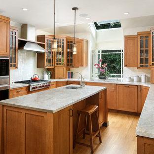 Foto på ett mellanstort amerikanskt u-kök, med en dubbel diskho, skåp i mellenmörkt trä, vitt stänkskydd, ljust trägolv, en köksö, luckor med glaspanel, rostfria vitvaror, stänkskydd i keramik och brunt golv