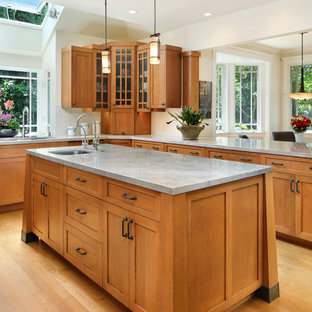 Inspiration for a mid-sized arts and crafts u-shaped eat-in kitchen in San Francisco with a double-bowl sink, glass-front cabinets, medium wood cabinets, white splashback, stainless steel appliances, light hardwood floors, with island and brown floor.