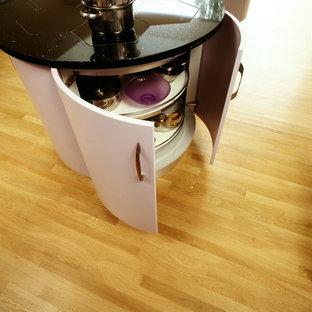 サリーの大きいコンテンポラリースタイルのおしゃれなキッチン (一体型シンク、フラットパネル扉のキャビネット、珪岩カウンター、ガラス板のキッチンパネル、淡色無垢フローリング) の写真