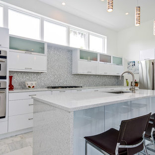 Large contemporary kitchen pictures - Inspiration for a large contemporary l-shaped kitchen remodel in Jacksonville with an undermount sink, glass-front cabinets, white cabinets and gray backsplash