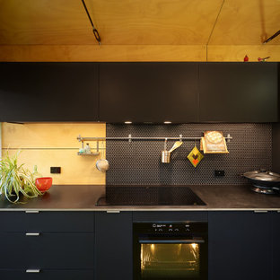 Inspiration for a mid-sized contemporary galley separate kitchen in Other with a drop-in sink, flat-panel cabinets, black cabinets, black splashback, black appliances, green floor, black benchtop, ceramic splashback, linoleum floors and timber.