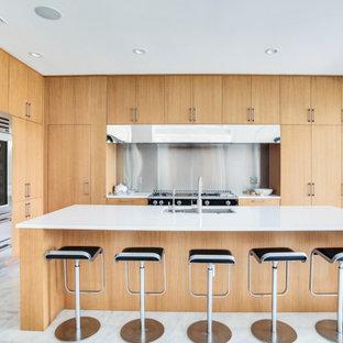 タンパの広いコンテンポラリースタイルのおしゃれなキッチン (アンダーカウンターシンク、フラットパネル扉のキャビネット、淡色木目調キャビネット、珪岩カウンター、シルバーの調理設備、大理石の床、白い床、白いキッチンカウンター、メタリックのキッチンパネル) の写真