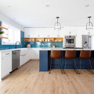Ispirazione per un'ampia cucina contemporanea con lavello stile country, ante in stile shaker, ante bianche, top in quarzo composito, paraspruzzi blu, paraspruzzi in gres porcellanato, elettrodomestici in acciaio inossidabile, pavimento in vinile, top bianco, isola e pavimento beige