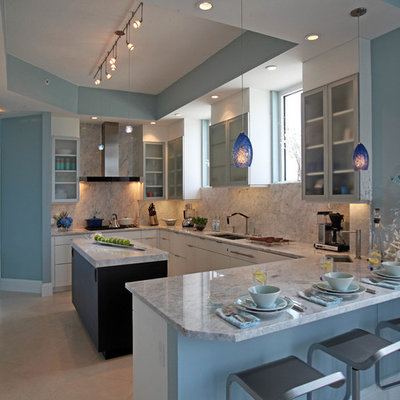 Example of a large trendy u-shaped porcelain tile eat-in kitchen design in Miami with flat-panel cabinets, white cabinets, granite countertops, stone slab backsplash, paneled appliances, an island, an undermount sink and gray backsplash
