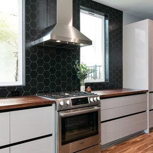 ロサンゼルスの中サイズのコンテンポラリースタイルのおしゃれなキッチン (アンダーカウンターシンク、フラットパネル扉のキャビネット、グレーのキャビネット、木材カウンター、黒いキッチンパネル、磁器タイルのキッチンパネル、シルバーの調理設備の、クッションフロア、マルチカラーの床、茶色いキッチンカウンター) の写真