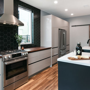 ロサンゼルスの中サイズのコンテンポラリースタイルのおしゃれなキッチン (アンダーカウンターシンク、フラットパネル扉のキャビネット、グレーのキャビネット、クオーツストーンカウンター、黒いキッチンパネル、磁器タイルのキッチンパネル、シルバーの調理設備の、クッションフロア、マルチカラーの床、白いキッチンカウンター) の写真