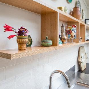 Kleine Eklektische Wohnküche in L-Form mit Doppelwaschbecken, offenen Schränken, Edelstahl-Arbeitsplatte, Küchenrückwand in Weiß, Rückwand aus Keramikfliesen, Küchengeräten aus Edelstahl, Betonboden und Kücheninsel in Wellington