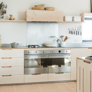 Design ideas for a mid-sized scandinavian l-shaped eat-in kitchen in Other with flat-panel cabinets, light wood cabinets, stainless steel benchtops, metallic splashback, stainless steel appliances, light hardwood floors, with island and a farmhouse sink.