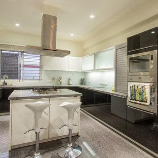 Идея дизайна: угловая кухня в современном стиле с плоскими фасадами, черными фасадами, фартуком из стекла, техникой из нержавеющей стали и островом
