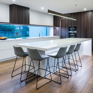 Inspiration for a contemporary l-shaped kitchen in Melbourne with a drop-in sink, flat-panel cabinets, quartz benchtops, window splashback, stainless steel appliances, medium hardwood floors, multiple islands, brown floor and white benchtop.