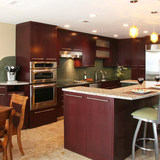 This is an example of a mid-sized contemporary l-shaped eat-in kitchen in Chicago with an undermount sink, flat-panel cabinets, dark wood cabinets, recycled glass benchtops, green splashback, glass tile splashback, stainless steel appliances, limestone floors and with island.