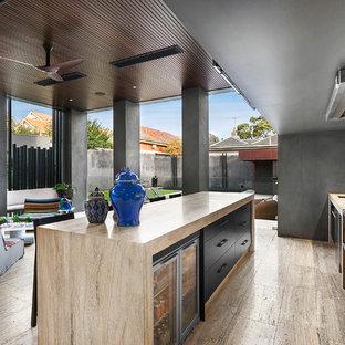 Ispirazione per una cucina contemporanea con lavello sottopiano, ante lisce, ante nere, paraspruzzi beige, elettrodomestici in acciaio inossidabile e isola