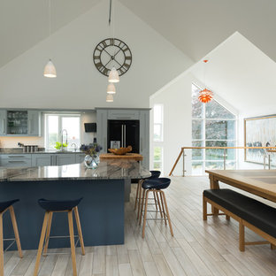 Design ideas for a large contemporary l-shaped kitchen/diner in West Midlands with recessed-panel cabinets, blue cabinets, black appliances, light hardwood flooring, an island, a submerged sink and marble worktops.