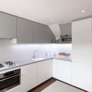 ロンドンの小さい北欧スタイルのおしゃれなキッチン (ドロップインシンク、フラットパネル扉のキャビネット、白いキャビネット、人工大理石カウンター、白いキッチンパネル、モザイクタイルのキッチンパネル、シルバーの調理設備の、濃色無垢フローリング) の写真