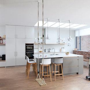 Modern inredning av ett mellanstort kök med öppen planlösning, med en köksö