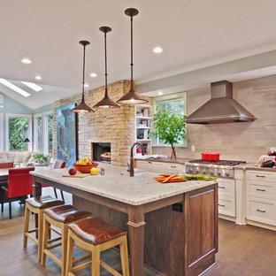 Inredning av ett klassiskt stort kök, med en rustik diskho, skåp i shakerstil, vita skåp, bänkskiva i kvarts, grått stänkskydd, rostfria vitvaror, en köksö, mellanmörkt trägolv och stänkskydd i kalk