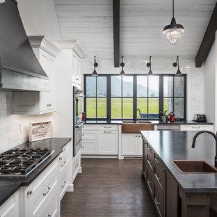 バンクーバーの巨大なカントリー風おしゃれなキッチン (エプロンフロントシンク、シェーカースタイル扉のキャビネット、白いキャビネット、ラミネートカウンター、白いキッチンパネル、大理石の床、シルバーの調理設備の、濃色無垢フローリング、茶色い床) の写真