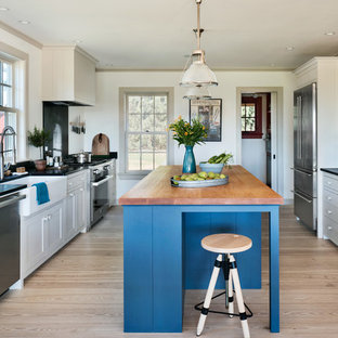 Traditional kitchen inspiration - Kitchen - traditional light wood floor kitchen idea in New York with a farmhouse sink, shaker cabinets, beige cabinets, wood countertops, stainless steel appliances, an island and black backsplash