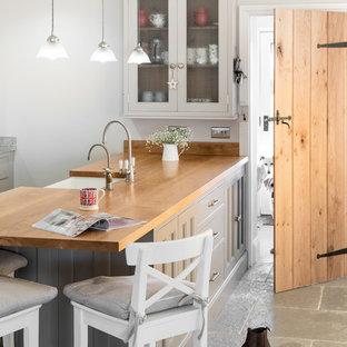 Foto på ett mellanstort lantligt kök och matrum, med grå skåp och en köksö