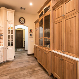 Inspiration for a large country u-shaped open plan kitchen in Phoenix with a farmhouse sink, raised-panel cabinets, beige cabinets, marble benchtops, panelled appliances, travertine floors, with island, brown floor and white benchtop.