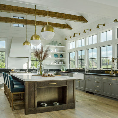 Example of a country l-shaped light wood floor kitchen design in Burlington with a farmhouse sink, shaker cabinets, gray cabinets and an island