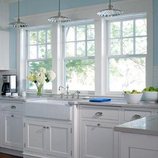 Inredning av ett lantligt litet, avskilt kök, med vita skåp, bänkskiva i kvartsit och en rustik diskho