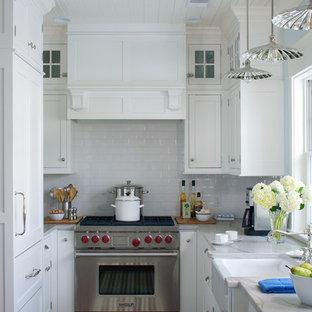 Imagen de cocina en U, campestre, pequeña, cerrada, con puertas de armario blancas, encimera de cuarcita, salpicadero blanco, salpicadero de azulejos tipo metro, electrodomésticos de acero inoxidable y fregadero sobremueble