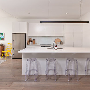 Inspiration for a mid-sized scandinavian single-wall eat-in kitchen in Other with a double-bowl sink, flat-panel cabinets, white cabinets, quartz benchtops, white splashback, glass sheet splashback, stainless steel appliances, laminate floors, with island, grey floor and white benchtop.