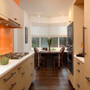 ワシントンD.C.の中くらいのコンテンポラリースタイルのおしゃれなII型キッチン (フラットパネル扉のキャビネット、中間色木目調キャビネット、オレンジのキッチンパネル、ガラス板のキッチンパネル、黒い調理設備、無垢フローリング、アイランドなし、茶色い床、白いキッチンカウンター) の写真