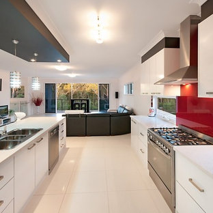Large contemporary open concept kitchen inspiration - Large trendy galley porcelain floor and white floor open concept kitchen photo in Brisbane with a triple-bowl sink, white cabinets, quartz countertops, red backsplash, glass sheet backsplash, stainless steel appliances and an island