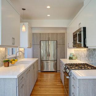 Zweizeilige, Kleine Moderne Wohnküche mit Waschbecken, flächenbündigen Schrankfronten, grauen Schränken, Mineralwerkstoff-Arbeitsplatte, Küchenrückwand in Grau, Rückwand aus Glasfliesen, Küchengeräten aus Edelstahl und hellem Holzboden in San Francisco