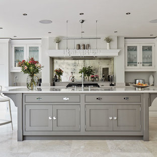 This is an example of a large transitional l-shaped eat-in kitchen in Manchester with an integrated sink, shaker cabinets, grey cabinets, quartzite benchtops, metallic splashback, mirror splashback, coloured appliances, marble floors, with island, beige floor and white benchtop.