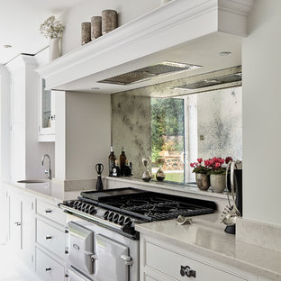 Large contemporary l-shaped eat-in kitchen in Manchester with an integrated sink, shaker cabinets, grey cabinets, quartzite benchtops, metallic splashback, mirror splashback, coloured appliances, marble floors, with island, beige floor and white benchtop.