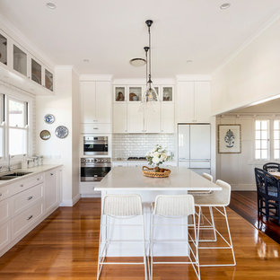 Traditional l-shaped kitchen in Brisbane with an undermount sink, shaker cabinets, white cabinets, white splashback, stainless steel appliances, medium hardwood floors, with island, brown floor and white benchtop.